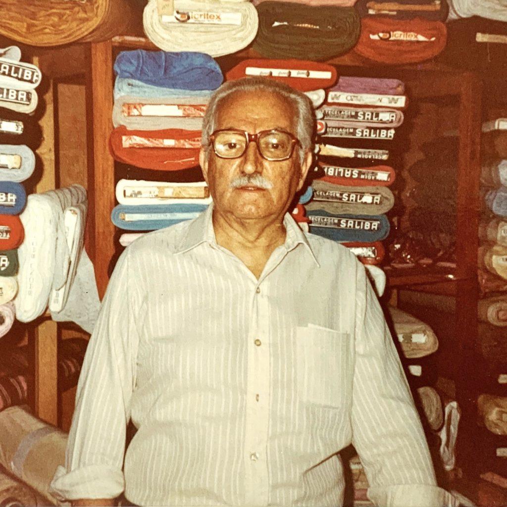 Nossa história: Imagem do fundador Salah Saliby em frente aos tecidos da loja.