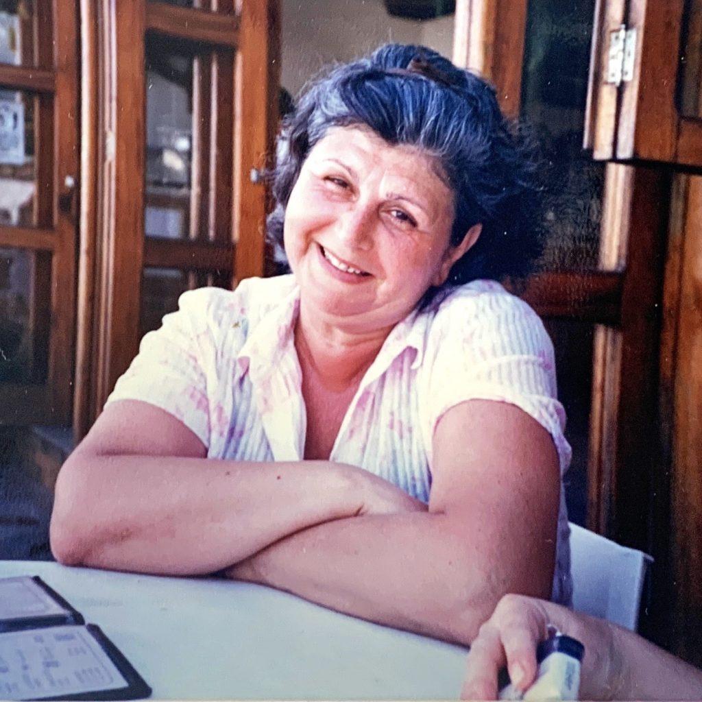 Nossa história: Imagem da fundadora Iracema Saliby sorrindo em um salão de restaurante.