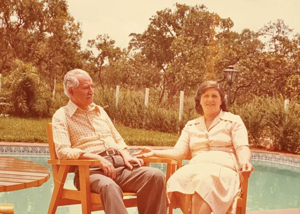Imagem dos fundadores Salah Saliby e Iracema Saliby de mãos sentados em cadeiras de madeira.