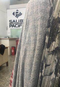 imagem da entrada da empresa Saliby Pacific - Rei dos Veludos, com dois tipos de tecidos a frente e o logo no fundo.