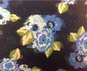 Tecido de algodão estampado floral, com fundo preto e flores brancas e azuis.